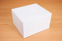 Caja blanca en blanco en el fondo de madera Imagenes de archivo