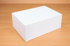Caja blanca en blanco en el fondo de madera Imagen de archivo