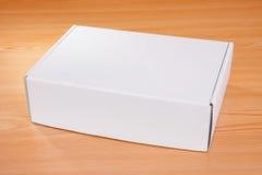 Caja blanca en blanco en la madera Imagenes de archivo