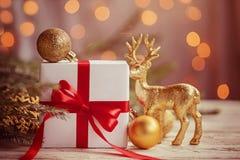 Caja blanca o presente con las bolas de oro y ciervos de la Navidad en la tabla de madera tono de imagen imagen de archivo libre de regalías