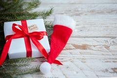 Caja blanca o presente de la Navidad con la cinta roja para santa secreto con el sombrero de santa en la tabla de madera foto de archivo