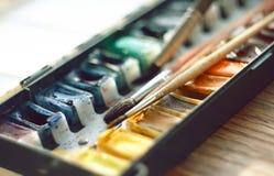 Caja con la acuarela en cubetas y cepillos imágenes de archivo libres de regalías
