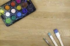 Caja con las acuarelas y los cepillos en superficie de madera Imágenes de archivo libres de regalías