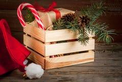 Caja con las decoraciones de la Navidad, las ramas de árbol de navidad y el regalo Foto de archivo