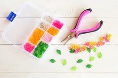 Caja con las gotas, las flores plásticas y los accesorios para la joyería de la mano en el fondo de madera blanco alicates Imágenes de archivo libres de regalías