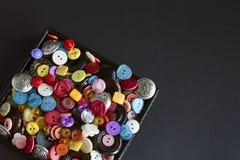 Caja con los botones multicolores en fondo negro fotografía de archivo