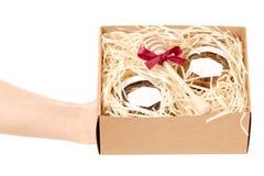 Caja con los tarros del regalo determinado de la miel presente en las manos aisladas Foto de archivo