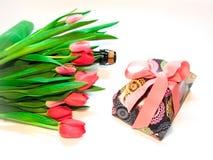 Caja con un regalo, los tulipanes y el champán Foto de archivo