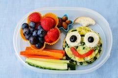 Caja de almuerzo escolar para los niños con la comida bajo la forma de caras divertidas Imagen de archivo