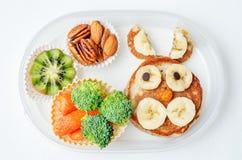 Caja de almuerzo escolar para los niños con la comida bajo la forma de caras divertidas Imagen de archivo libre de regalías