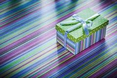 Caja de cartón con el regalo en concepto rayado de las celebraciones de la tela Imagen de archivo libre de regalías