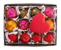Caja de cartón con las bolas de la Navidad en células, corazón del juguete arriba, en blanco Foto de archivo