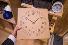 Caja de cartón con un reloj en él Foto de archivo
