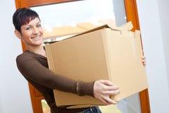 Caja de cartón de elevación de la mujer joven Imágenes de archivo libres de regalías