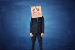 Caja de cartón del hombre de negocios que lleva con la cara triste exhausta en su cabeza Imagenes de archivo