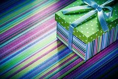 Caja de cartón envuelta con el regalo en celebratio rayado del mantel Foto de archivo