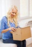 Caja de cartón sonriente de la abertura de la mujer en casa fotografía de archivo