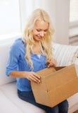 Caja de cartón sonriente de la abertura de la mujer joven en casa Fotos de archivo