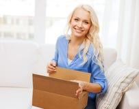 Caja de cartón sonriente de la abertura de la mujer joven en casa Imagen de archivo