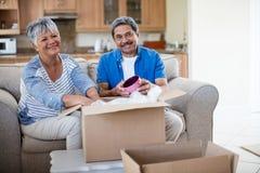 Caja de cartón unpackaging de los pares mayores en sala de estar en casa imagen de archivo libre de regalías