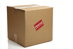 Caja de cartón cerrada en blanco con una etiqueta engomada frágil Fotos de archivo libres de regalías