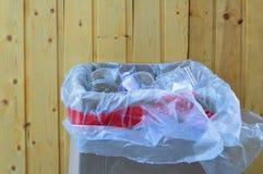 Caja de cartulina con basura en un fondo de madera En la calle foto de archivo
