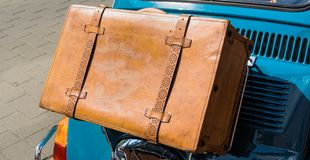Caja de cuero marrón antigua en el puente en la aleta del capo en la parte posterior de un pequeño coche imagen de archivo