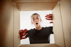 Caja de desempaque y de apertura de la mujer del cartón y que mira dentro foto de archivo