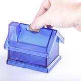 Caja de dinero azul de la casa con la mano del hombre y moneda en el fondo blanco Imágenes de archivo libres de regalías