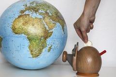 Caja de dinero con el globo del mundo Fotografía de archivo