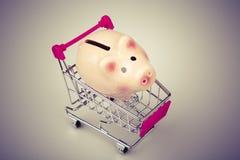 Caja de dinero del cerdo en carro de la compra en el fondo blanco Fotos de archivo libres de regalías