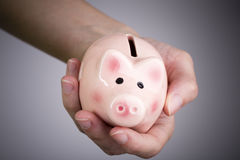 Caja de dinero del cerdo en mano de la mujer foto de archivo