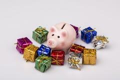 Caja de dinero del cerdo entre el regalo de la Navidad Imágenes de archivo libres de regalías