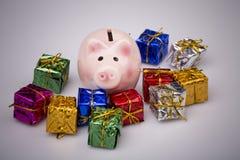 Caja de dinero del cerdo entre el regalo de la Navidad Imagen de archivo libre de regalías