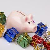 Caja de dinero del cerdo entre el regalo de la Navidad Imagen de archivo