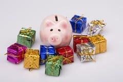 Caja de dinero del cerdo entre el regalo de la Navidad Fotografía de archivo libre de regalías