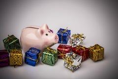 Caja de dinero del cerdo entre el regalo de la Navidad Foto de archivo