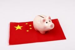 Caja de dinero del cerdo y bandera de China Fotografía de archivo