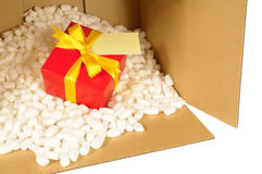 Caja de embalaje de la cartulina con el regalo rojo dentro, nueces del poliestireno, etiqueta de dirección Imágenes de archivo libres de regalías