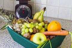 Caja de fruta y verdura en la tabla de cocina Fotografía de archivo