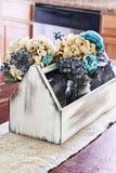 Caja de herramientas antigua de madera con las flores en la tabla del cortijo Fotos de archivo