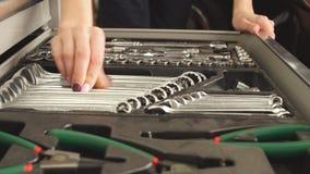 Caja de herramientas femenina de Taking Instruments From del mec?nico en garaje de la reparaci?n metrajes