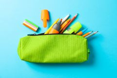 Caja de lápiz con las fuentes de escuela en fondo azul foto de archivo