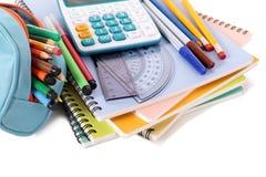 Caja de lápiz, fuentes de escuela con la calculadora, pila de libros, aislada en el fondo blanco Imagen de archivo libre de regalías