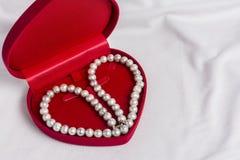 Caja de la caja blanca de la perla y de joya en la tela blanca Imágenes de archivo libres de regalías