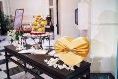 Caja de la forma del corazón en color oro en el frente de la recepción nupcial con el libro de la muestra fotografía de archivo libre de regalías