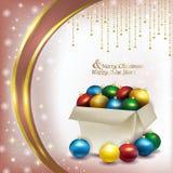 Caja de la Navidad con las bolas coloreadas en fondo rosado Foto de archivo