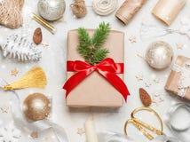 Caja de la Navidad o de regalo del Año Nuevo adornada con el arco rojo brillante y la diversa decoración de la Navidad alrededor  Fotografía de archivo