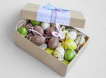 Caja de las decoraciones de Pascua con los huevos pintados, los conejitos de papel y el flujo Imagen de archivo libre de regalías