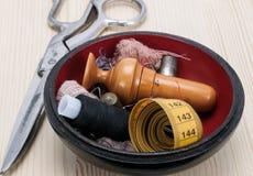 Caja de madera con accesorios de costura y un par de tijeras Fotos de archivo libres de regalías